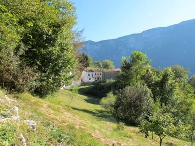Dal fitto del verde, improvvisamente fa capolino Borgo Caloniche di Sotto, al di la di un prato soleggiato.