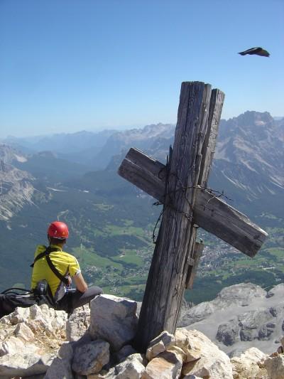 La croce della cima Tofana di Dentro, un corvazzo ed un escursionista.