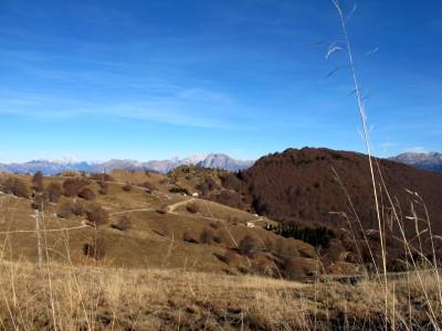 Dalla cima del monte Pizzoc possiamo già vedere il profilo che seguiremo e la collina boscosa dietro cui si nasconde casera Pian de la Pita.