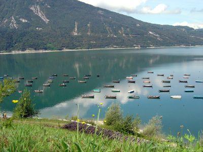 Vista sul lago di Santa Croce e sulle barche multicolore presso la spiaggetta in zona Poiatte.