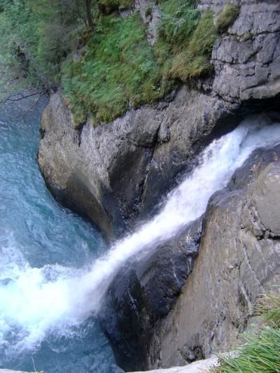 L'ultimo salto spinge l'acqua all'esterno, fuori dalla roccia, a formare un tranquillo torrente che segna il fondovalle.